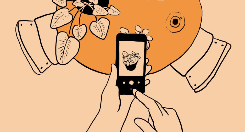Cilvēka rokas, kas tur telefonu un fotogrāfē augu, kas atrodas uz galda. Blakus galdam atrodas divi krēsli un virs tā vēl viens augs un kafijas tasīte.